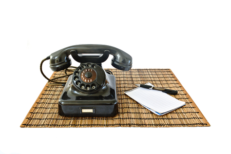 Vintage telephone on rattan mat with black pen and notepad with copyspace isolated on white background