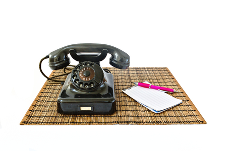 Vintage telephone on rattan mat with pink pen and notepad with copyspace isolated on white background
