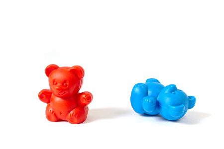 Red plastic toy bear standing with blue plastic toy bear knocked over Stock Photo