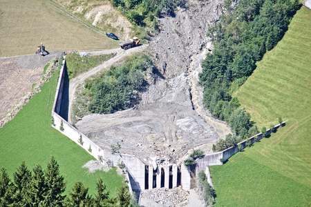Aerial view of mountain stream in the Austrian Alps blocked after a massive mudflow with excavator and truck working to clean up the site Stock Photo