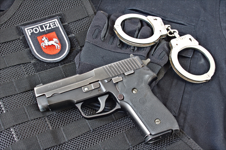 german handgun: Handgun with handcuff, gloves on blue uniform shirt and tactical vest with patch of Niedersachsen State Police, Germany