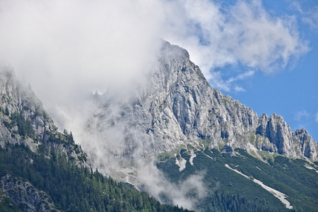 Rocky steep slope of a mountain partly covered by mist in the Tennen range in the Austrian Alps near the town of Werfen