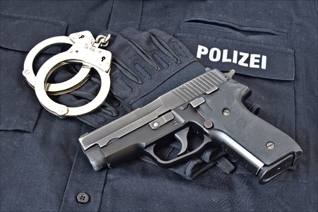 german handgun: Handgun with handcuffs and gloves on blue uniform shirt with Police in German on it Stock Photo