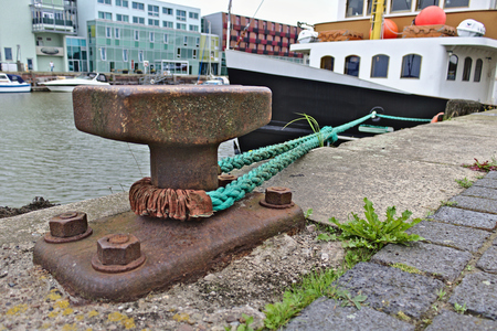 Rusty bollard with green mooring line leading to a ship alongside the pier and modern buildings in the background, Bremerhaven fishing port, Germany Stock Photo
