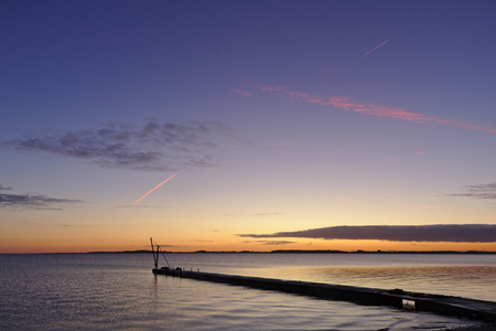 Pier before sunrise with small crane silhouetted against the morning sky and bright red vapor trail overhead