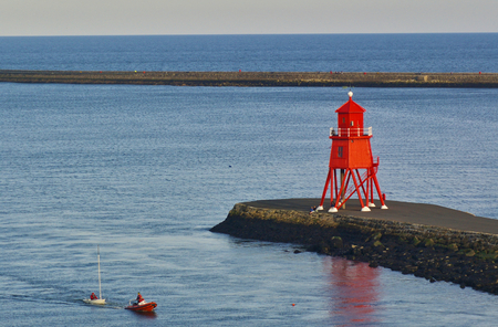 Newcastle, United Kingdom - October 5th, 2014 - Becalmed sailing dinghy in the mouth of the river Tyne is being towed ashore by a RIB next to a breakwater with a large red lighthouse