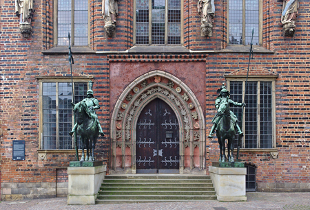 Bremen, Germany - November 7th, 2017 - Side entrance to the historic city hall with two metal statues of mounted knights Editorial