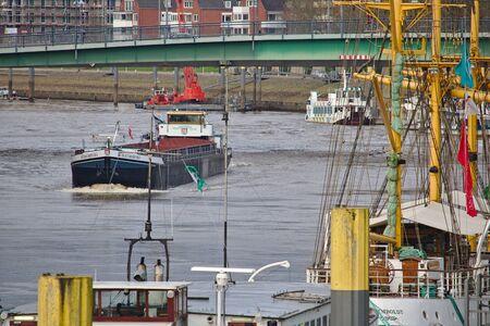 Bremen, Duitsland - 23 november 2017 - Binnenvaartschip passerende een brug over de rivier de Weser met residentiële gebouwen op de achtergrond en afgemeerd zeilschepen op de voorgrond