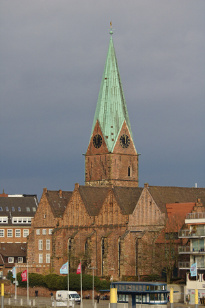 Bremen, Germany - November 23rd, 2017 - Historic St. Martin's church with tall spire and rain clouds in the background