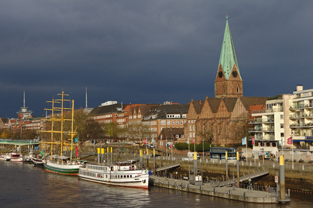 Riverside view of Bremen, Germany with moored ships, historic church, residential buildings and dark rain clouds in the background