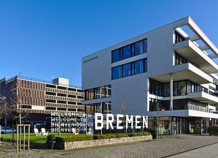 Bremen, Germany - November 25th, 2017 - Esplanade in the Ãœberseestadt district with five-story modern office building next to a large metal sign Welcome to Bremen in German, English, Spanish and French