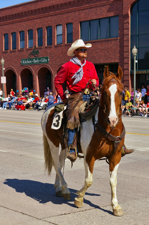 Cody, Wyoming, USA - Cowboy with bright red shirt riding on the Independence Day Parade 報道画像
