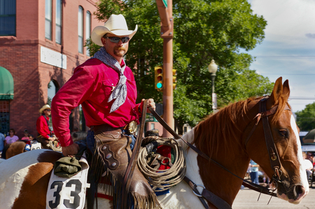 Cody, Wyoming, USA - Cowboy with bright red shirt riding on the Independence Day Parade Editorial
