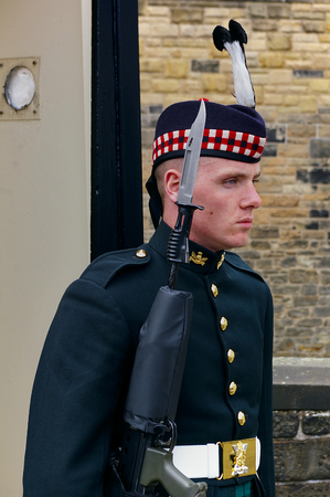 Edinburgh, Scotland - June 2nd, 2012 - Soldier of the Royal Regiment of Scotland in full dress uniform carrying his rifle with fixed bayonet guarding the entrance of Edinburgh Castle