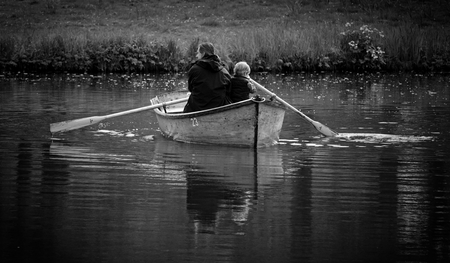 Bremen, Germany - April 20th, 2017 - Father and son rowing a boat together on the lake in the Bürgerpark 新聞圖片