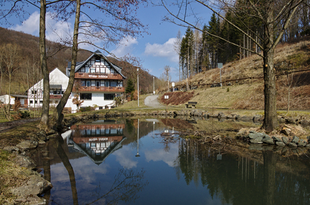 Willingen, Germany - March 27th, 2018 - Traditional timber-framed and whitewashed farm building reflecting in the pond