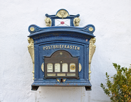 Gluecksburg, Germany - April 8th, 2018 - Vintage German mailbox mounted on a white washed wall beside a green bush