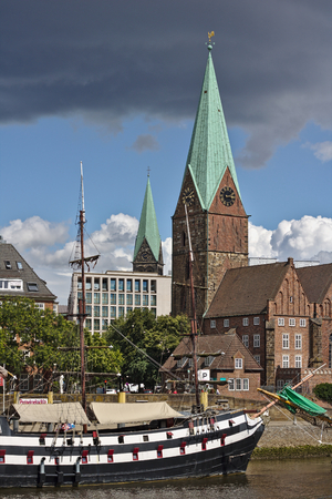 Bremen, Germany - July 10th, 2018 - Sailing ship at her moorings with St. Martini church in the background (portrait)