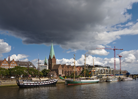 Bremen, Germany - July 10th, 2018 - Riverside view of the Schlachte promenade and the sailing ship Alexander von Humboldt at her moorings with the St. Martini church and a large construction site in the background 新聞圖片