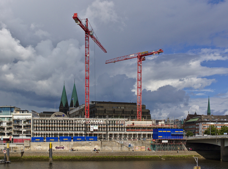 Bremen, Germany - July 10th, 2018 - Construction site of the new Kuehne building on the bank of the river Weser with huge cranes and church spires in the distance 新聞圖片