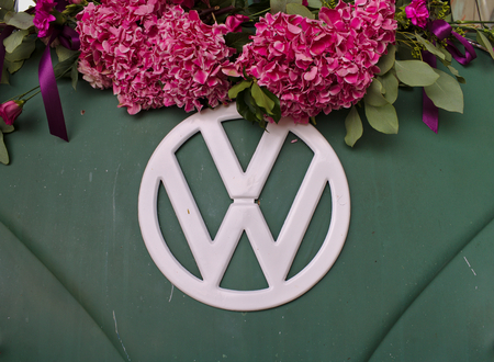 Bremen, Germany - July 17th, 2018 - Close-up photo of the front of a green VW T3 van with white VW logo decorated with pink flowers 新聞圖片