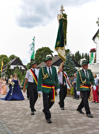 Usseln, Germany - July 29th, 2018 - Rifle club members in their traditional green uniforms carry a large flag at a parade at the marksmens fair 新聞圖片