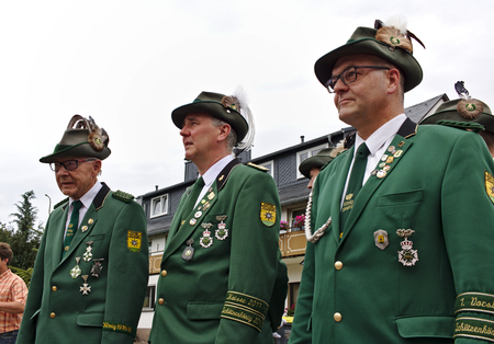 Usseln, Germany - July 29th, 2018 - Senior members of a rifle club wearing their traditional green uniforms at a parade at the marksmens fair