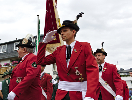 Usseln, Germany - July 29th, 2018 - Members of a rifle club wearing their traditional red uniforms salute at a parade at the marksmens fair