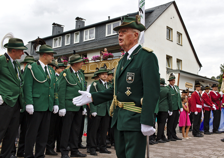 Usseln, Germany - July 29th, 2018 - A senior member of a rifle club adresses the ranks of his fellow club members in their traditional green uniforms at a parade at the marksmens fair