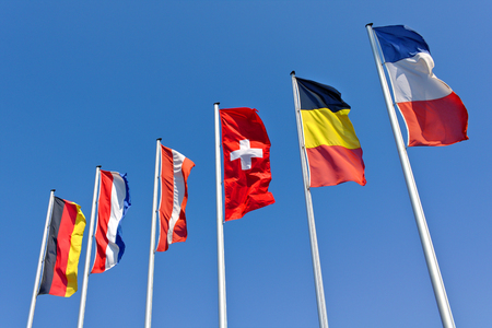 The national flags of Germany, the Netherlands, Austria, Switzerland, Belgium and France flying in front of a blue sky