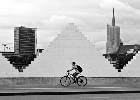 Bremen, Germany - August 14th, 2018 - A boy rides his bicycle on the sidewalk while passing a white triangle-shaped brick wall framed by a church and a high-rise building in the distance (monochrome)