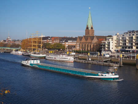 Bremen, Germany - November 17th, 2018 - River Weser with historic waterfront, moored ships and cargo vessel passing by