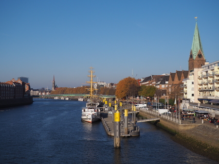 Bremen, Germany - View of the river Weser and the historic Schlachte waterfront with the spire of St. Martini church