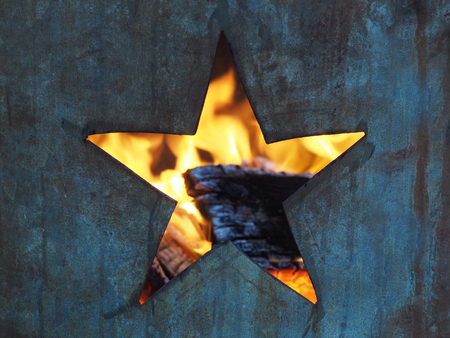 Hole in the shape of a five-pointed star cut into a metal burning barrel with flames and burned wood visible inside