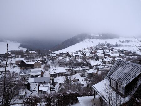 Sauerland, Germany - View over snow-covered small town with wooded hills and low hanging clouds in the background 版權商用圖片