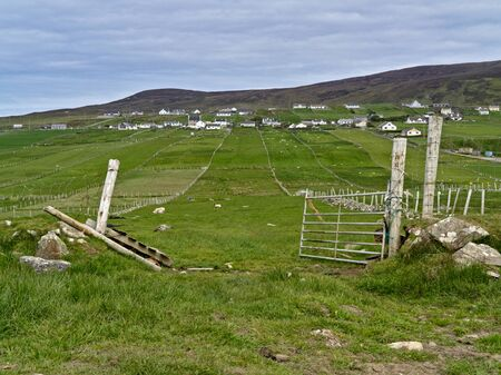 Green pasture with fence and open gate in the foreground and the village of Malinbeg in the background.