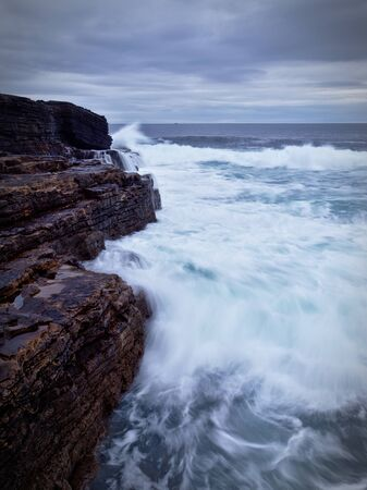Waves crashing on the brown rocky cliffs of the Irish west coast at dusk (long exposure, portrait)