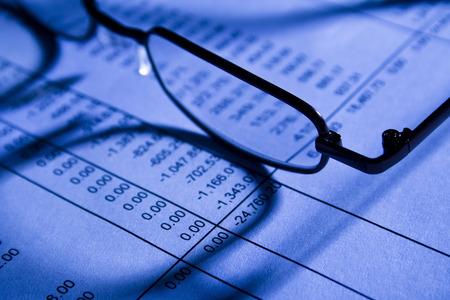 hoja de calculo: Gafas en oficina en la hoja de c�lculo financiero Foto de archivo