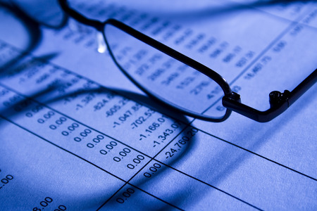scrutiny: Glasses In Office On Financial Spreadsheet Stock Photo