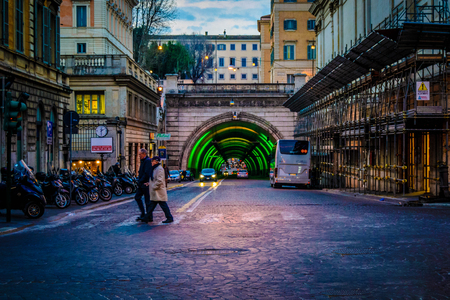 Two people walking in Rome, its 6 past mornig the end work time for citizens, sun will goes down quickly and cars ride the trafic leaving the city capitol to go home. lights starting 15 minute before six past morning.