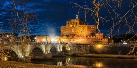 Ina clody blue night a fantastic view of Castel sant Angelo from the Tiber river, blue and yellow colors Stock Photo