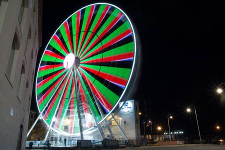 Panoramic wheel in the night. Colored modern ferris wheel tourist attraction