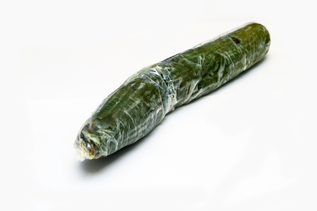 A picture of a rotten cucumber packed in the plastic foil. The foil is useless, it only damages the vegetable and it only goes mouldy. Isolated on a white background. Imagens