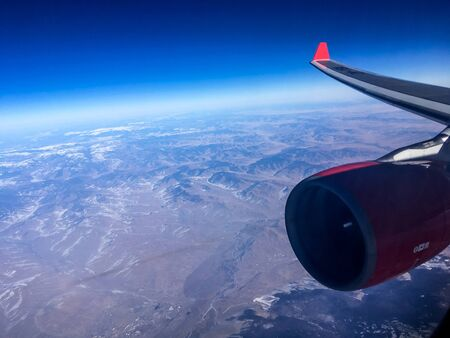 An aerial view from the airplane flying high above the ground. A look from the plane´s window with engine and wing visible.