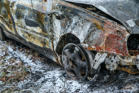 Car destroyed during the traffic accident. It was caused by the bad weather conditions in winter, because of the black ice or snow. The car is burnt, abandoned and stands by the road in the snowfall. Reklamní fotografie