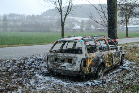Car destroyed during the traffic accident. It was caused by the bad weather conditions in winter, because of the black ice or snow. The car is burnt, abandoned and stands by the road in the snowfall. Stock Photo