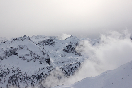 A picture from the Alps in Austria. A view on peaks and valleys covered by snow and mist.