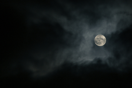 A full moon behind the clouds during the cloudy night. It is hiding and is visible only for few seconds.