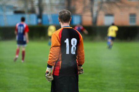 A goalkeeper is standing and looking on his team mates playing the footbal match. Banco de Imagens