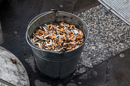 A picture of a public ashtray. The bucket with sand. Looks ugly and like a mess.